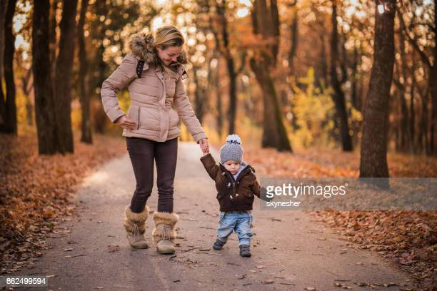 happy mom enjoy her sons first steps in park on autumn