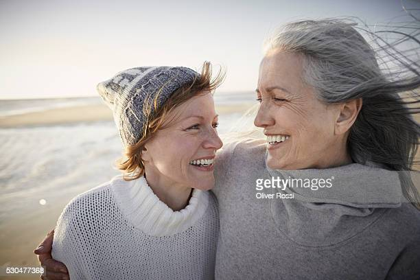 Happy mother and adult daughter on beach
