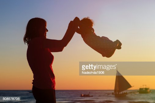 happy mother and baby having fun at sunset beach : Stock Photo