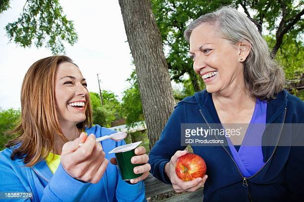 Happy Mother and Daughter Eating Healthy At a Park Bench