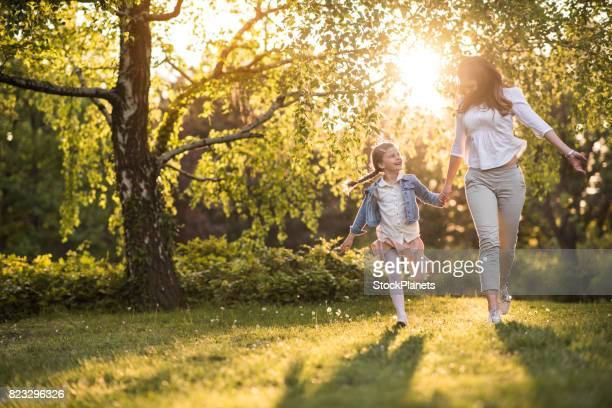 Happy mother and daughter having fun while holding hands and running in the park.