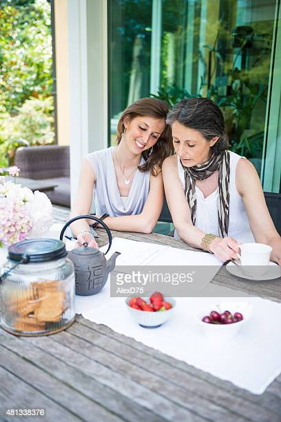 Happy mother and daughter having tea outdoor