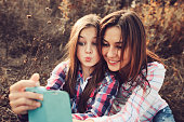 happy mother and daughter making selfie outdoor in summer. Happy family spending summer vacation together outdoor. Cozy warm mood, lifestyle capture.happy mother and daughter making selfie outdoor in