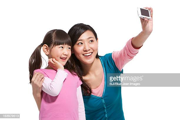 Happy mother and daughter photographing themselves