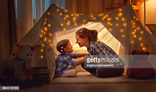 happy mother and daughter playing at home in tent : Foto de stock