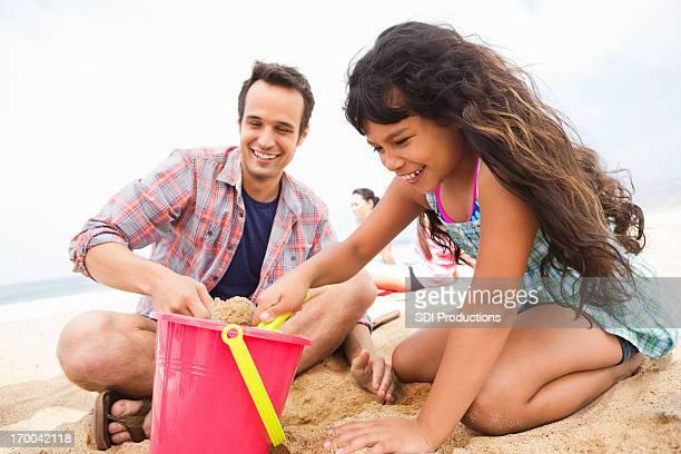 Felice Madre e figlia giocano con la sabbia sulla spiaggia