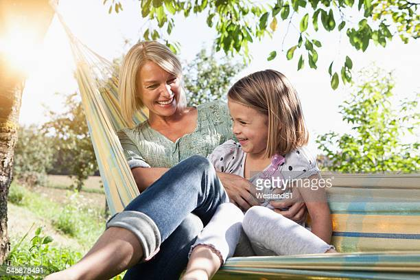 Happy mother and daughter sitting in hammock