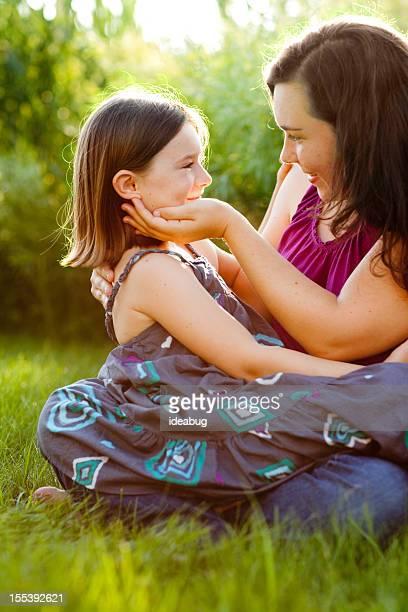 Glückliche Mutter und Tochter sitzen zusammen