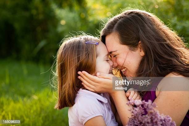 Happy Mother and Daughter Smiling While Touching Noses Outside