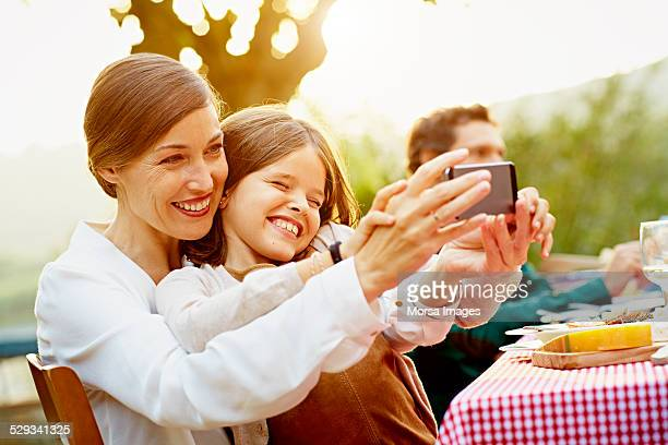 Happy mother and daughter taking selfie in yard