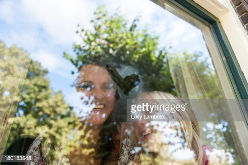 Happy mother and daughter with heart on window : Stockfoto