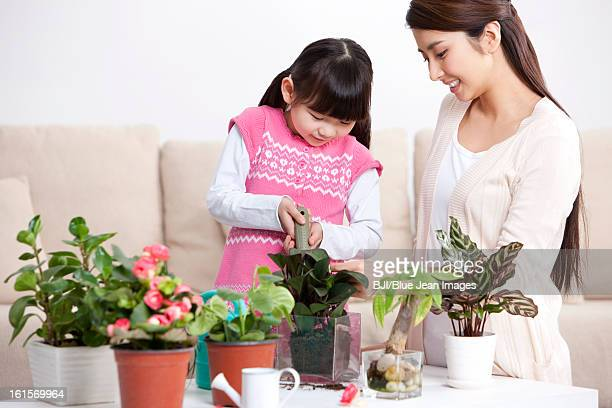 Happy mother and daughter with potted plants