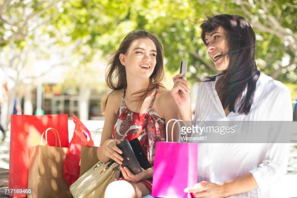 Happy mother and daughter with shopping bags and credit card in the city