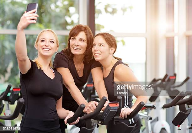 happy mother and daughters taking selfie in gym