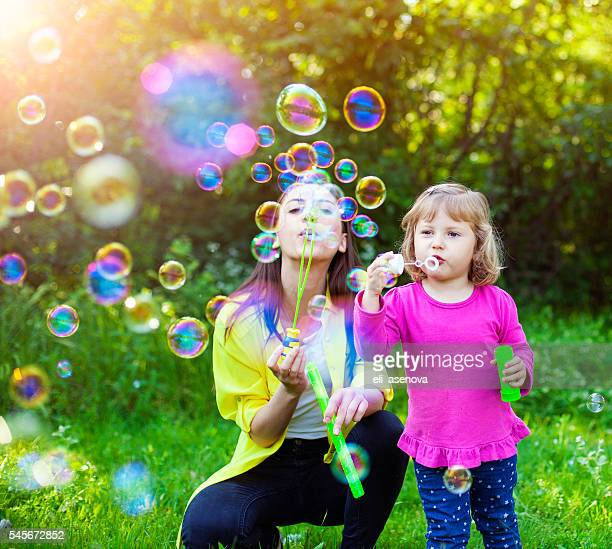 Happy mother and her child playing with Soap Bubbles