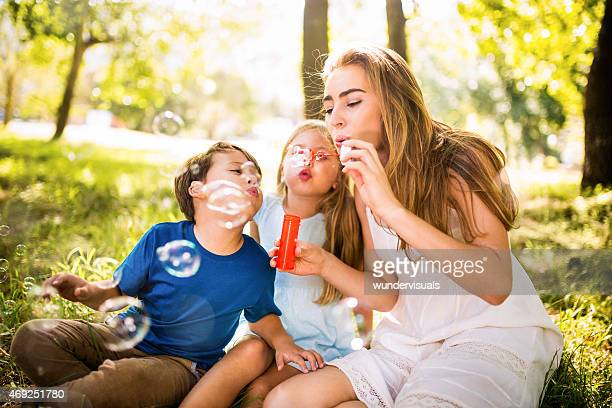 Happy mother and her kids blowing bubbles in a park