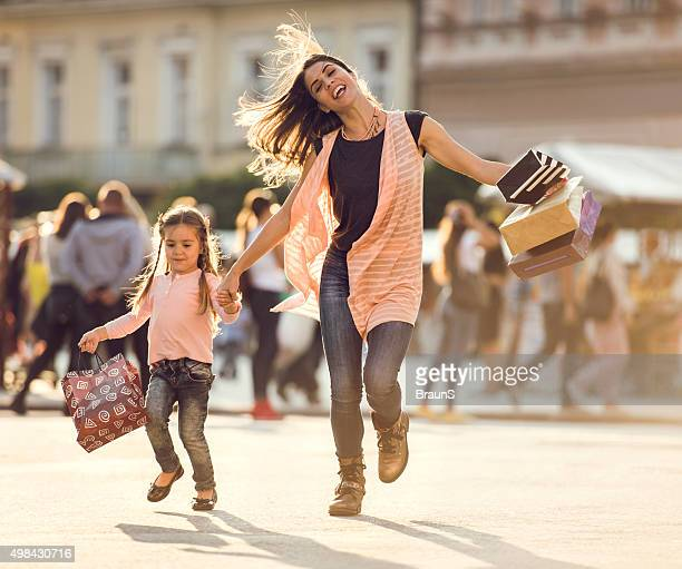 Happy mother and little daughter running with shopping bags.