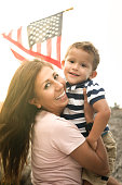 Happy immigrant mother holding her little boy with the american flag on the background