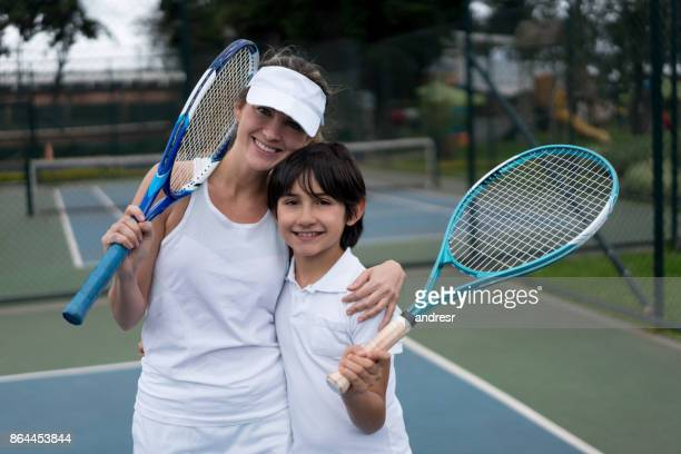 Happy mother and son playing tennis outdoors