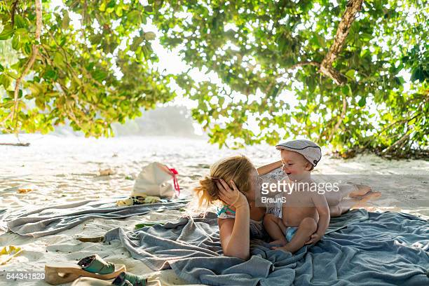 Happy mother and son relaxing in a shade at beach.