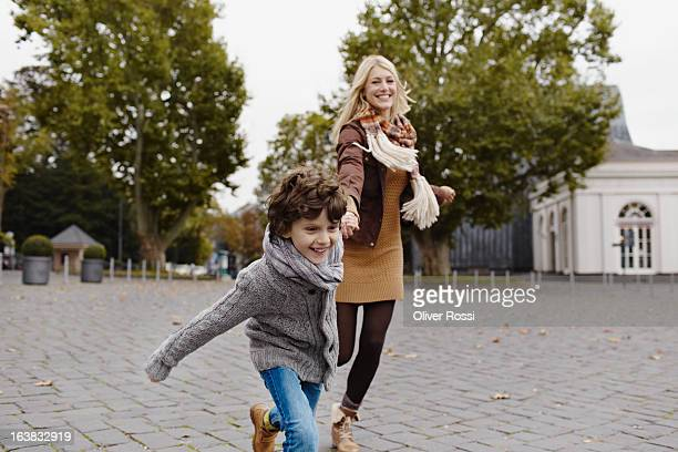 Happy mother and son running outdoors
