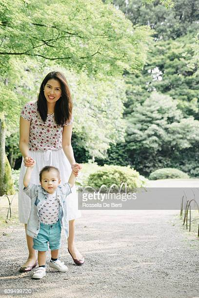 Happy mother and son walking together outdoors in a park