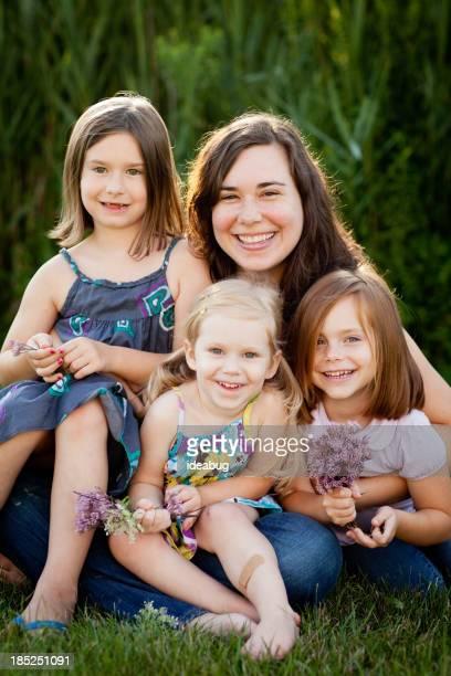 Heureuse mère et fille de trois séance ensemble à l'extérieur