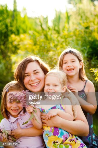 Happy Mother and Three Daughters Sitting Together Outside