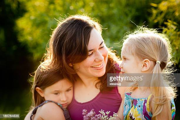 Happy Mother and Two Daughters Sitting Together Outside