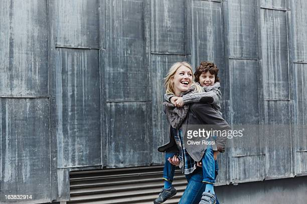 Happy mother carrying son piggyback
