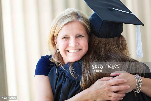 Happy Mother Congratulating Hugging Daughter in University Graduation Ceremony