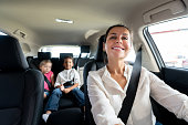 Portrait of a happy mother driving a car with her two kids while smiling - transportation concepts