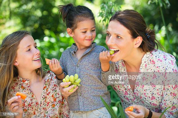 Happy mother eating fruits with her two daughters outdoors