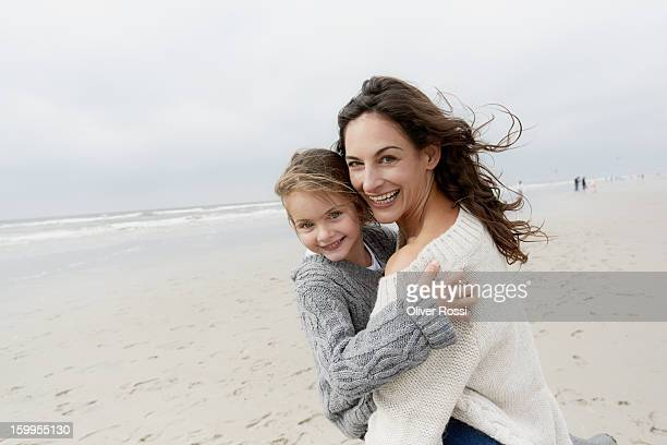 Happy mother embracing daughter on the beach