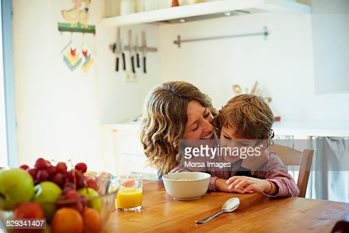 Happy mother embracing son having breakfast