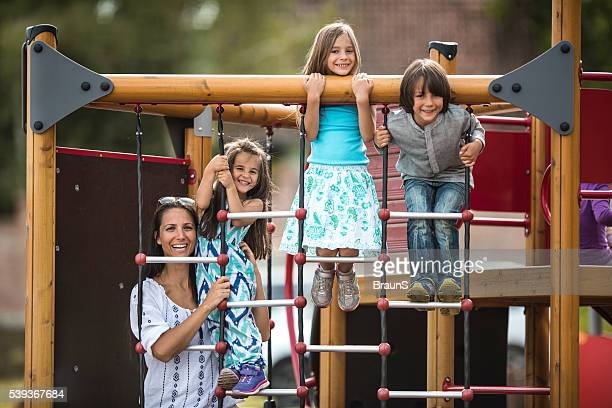 Heureuse mère avec ses enfants profiter sur un terrain de jeu.