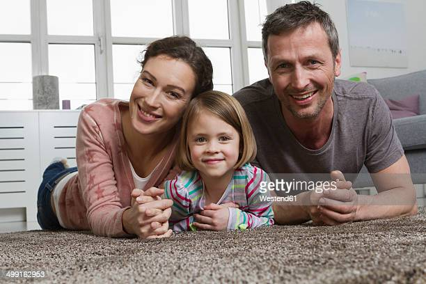 Happy mother, father and daughter lying on carpet in living room