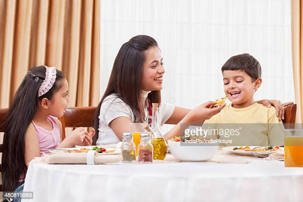 Happy mother feeding her son pizza with daughter sitting besides