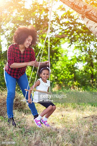 Happy mother having fun with your child on a swing