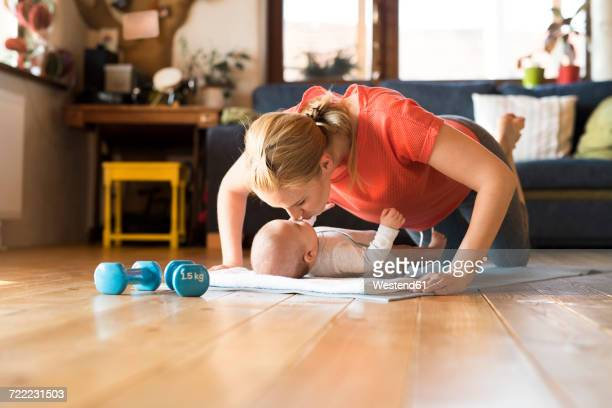Happy mother kissing baby at home lying on mat next to dumbbells