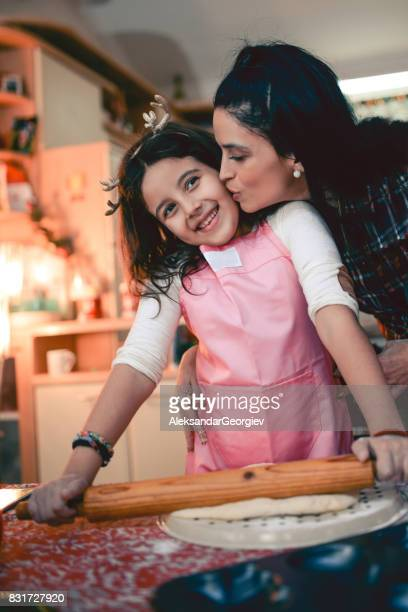 Happy Mother Kissing Little Daughter While She Make Cookies