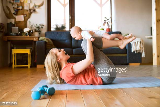 Happy mother lifting up baby at home lying on mat