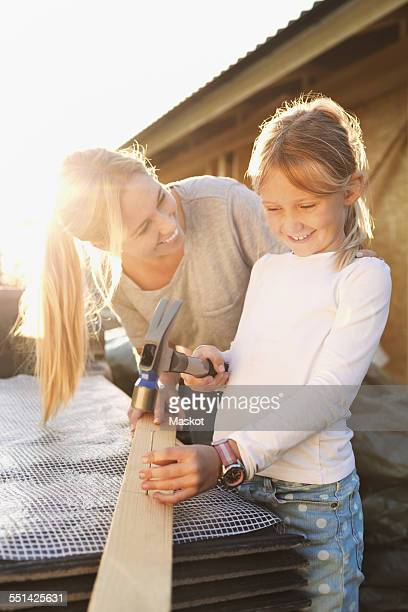 Happy mother looking at daughter hammering nail on plank outside house being renovated