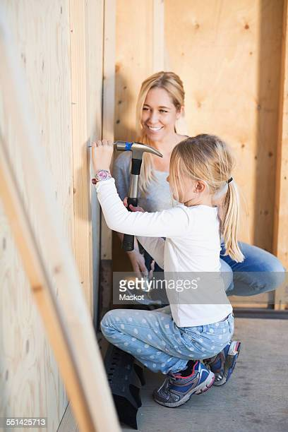 Happy mother looking at daughter hammering nail outside house being renovated