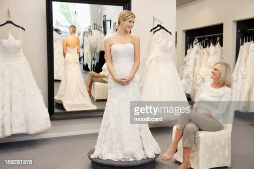 Happy mother looking at young daughter dressed in wedding gown in bridal boutique