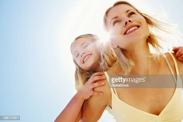 Happy mother piggybacking her daughter