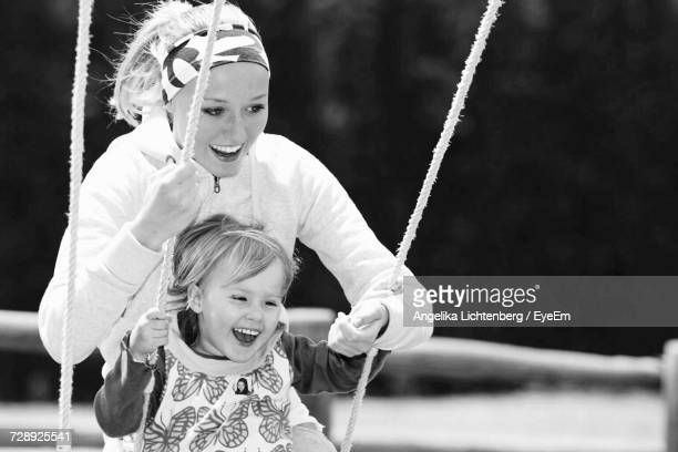 Happy Mother Pushing Daughter On Swing At Playground