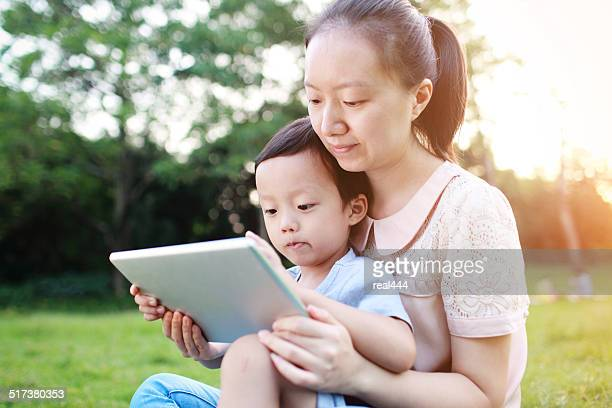 happy mother teaching little boy with tablet