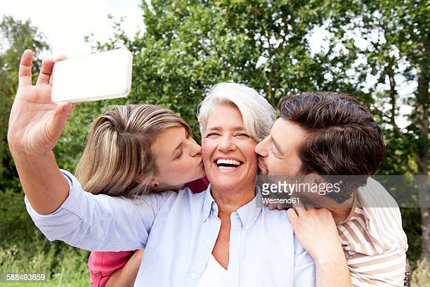 Happy mother with adult children taking cell phone picture outdoors