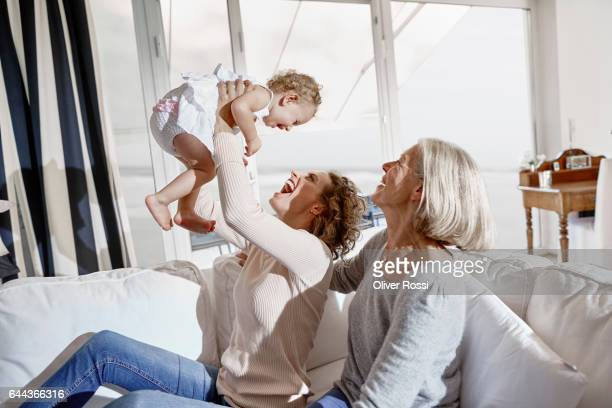 Happy mother with baby girl and grandmother at home